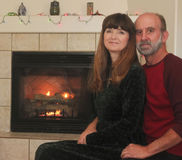 在一个壁炉前面的一对夫妇在圣诞节 免版税库存图片