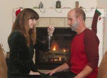 在一个壁炉前面的一对夫妇在圣诞节 免版税库存照片