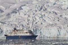 在一个夏日冰川的背景的蓝色旅游船 免版税库存照片