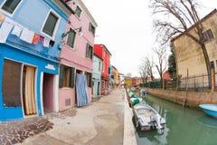 在一个多云冬日期间,在五颜六色的房子的宽看法从一条次要街道在Burano海岛 库存照片