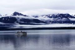 在一个多云山风景的在大洋里航行的船 图库摄影