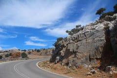 在一个多山风景的背景的柏油路 免版税图库摄影