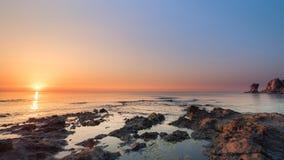 在一个多岩石的海滩和清楚的天空的日出 免版税库存照片
