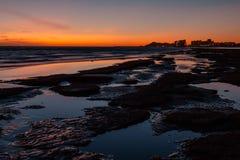 在一个多岩石的海滩的日落在前面旅馆 库存照片