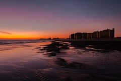 在一个多岩石的海滩的日落在前面旅馆 库存图片