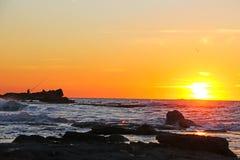 在一个多岩石的海滩的日落 库存图片