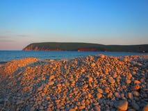 在一个多岩石的海滩的日落 免版税库存图片