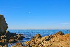 在一个多岩石的海滩附近的镇静蓝色海洋 图库摄影