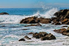 在一个多岩石的海滩附近的镇静蓝色海洋 免版税库存照片