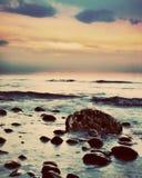 在一个多岩石的海滩的剧烈的日出。减速火箭,葡萄酒 免版税库存照片