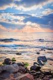 在一个多岩石的海滩的日出 反射在海的五颜六色的云彩 免版税库存图片