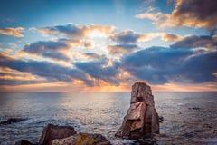 在一个多岩石的海滩的日出 反射在海的五颜六色的云彩 库存图片