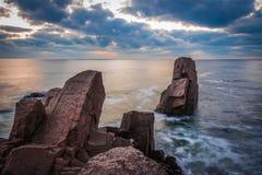 在一个多岩石的海滩的日出 反射在海的五颜六色的云彩 免版税库存照片