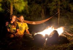 在一个多岩石的海滩的营火与夫妇开会 免版税库存图片