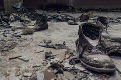 在一个多灰尘的地板上的老鞋子在一个兵连祸结的房子,在内部,灾害概念后果里面的被破坏的黑暗的大厦里  免版税库存照片