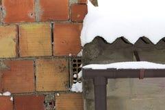 在一个多雪的屋顶附近的砖墙 库存图片