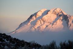 在一个多雪的山顶的日出 免版税库存图片