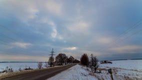 在一个多雪的领域的美好的风景在一条偏僻的路附近 每日timelapse 美丽的豪华的云彩漂浮在一个多雪的领域 股票视频