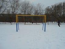 在一个多雪的领域的黄色蓝色橄榄球门 库存图片