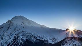 在一个多雪的高山风景的日落 免版税库存图片