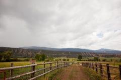 在一个大农场的土路有多云天空的 库存图片