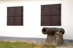 在一个大厦的背景墙壁上的古色古香的大炮与闭合的快门的 库存照片