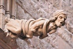 在一个大厦的面貌古怪的人在Carrer del Bisbe在Barri Gotic,巴塞罗那,西班牙 库存图片
