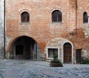 在一个大厦门面的一个古老砖墙的下中世纪街道曲拱在奇维达莱德尔夫留利镇  免版税图库摄影