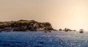 在一个大岩石和小船的日落 免版税库存照片