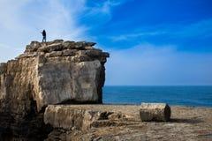 在一个大岩石的渔夫铸件 免版税库存照片