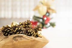 在一个大木碗的金黄闪烁锥体在一张白色木桌上 在一棵圣诞树的背景与光的 图库摄影