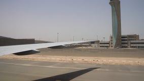 在一个大机场的到达的平面移动在沙漠 向船外明亮的太阳和清楚的天空 股票视频