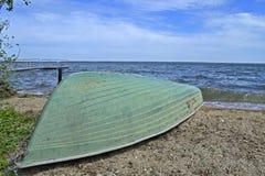 在一个大湖的岸的被倒置的小船 免版税库存图片