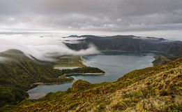 在一个大火山的火山口的看法与平衡的光的湖,在火山口外缘的云彩火车由长的曝光强调 库存图片
