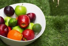 在一个大白色盘的绿色和红色苹果 库存图片