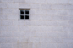 在一个大白色砖墙的小方形的窗口 库存图片