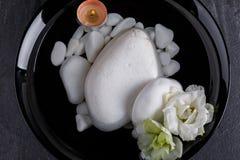 在一个大碗用水是不同地被塑造的小卵石和数燃烧的蜡烛 库存图片
