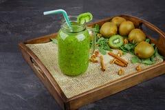 在一个大金属螺盖玻璃瓶的一个圆滑的人鸡尾酒 与新伐绿色猕猴桃和桂香的猕猴桃饮料在深灰背景 免版税库存图片