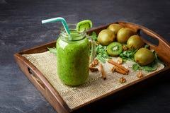 在一个大金属螺盖玻璃瓶的一个圆滑的人鸡尾酒 与新伐绿色猕猴桃和桂香的猕猴桃饮料在深灰背景 库存照片