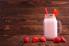在一个大金属螺盖玻璃瓶的一名刷新的草莓圆滑的人有红色秸杆和装饰草莓的在木背景 复制空间 库存照片