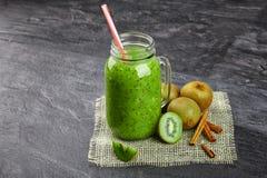 在一个大金属螺盖玻璃瓶的绿色圆滑的人饮料 与新伐绿色猕猴桃和桂香的刷新的饮料在灰色 免版税图库摄影