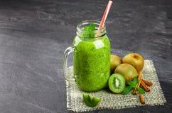 在一个大金属螺盖玻璃瓶的绿色圆滑的人饮料 与新伐绿色猕猴桃和桂香的刷新的饮料在灰色 库存图片