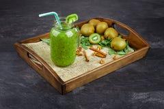 在一个大金属螺盖玻璃瓶的绿色浓饮料在深灰背景 在木盘子的猕猴桃圆滑的人 复制空间 库存照片