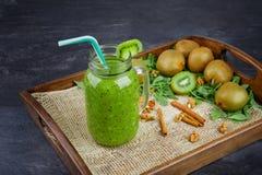 在一个大金属螺盖玻璃瓶的绿色浓饮料在深灰背景 在木盘子的猕猴桃圆滑的人 复制空间 库存图片