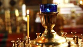 在一个大金黄法坛的一个灼烧的蜡烛在一个基督教会里 影视素材