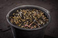 在一个大黑塑料桶是从枪的使用的多彩多姿的壳框 免版税图库摄影