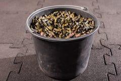 在一个大黑塑料桶是从枪的使用的多彩多姿的壳框 免版税库存照片