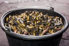 在一个大黑塑料桶是从枪的使用的多彩多姿的壳框 库存照片