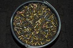 在一个大黑塑料桶是从枪的使用的多彩多姿的壳框 库存图片