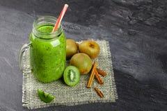 在一个大玻璃瓶子的绿色猕猴桃鸡尾酒 与新鲜的明亮的猕猴桃和桂香的刷新的厚实的饮料在灰色背景 免版税库存照片